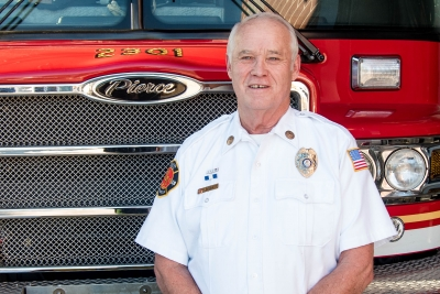 Fire chief in front of fire truck